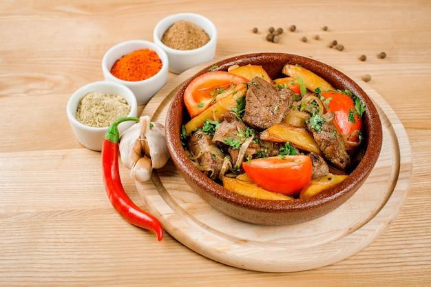 Ojahuri dans une assiette, décorée de poivre, ail, grains de poivre et épices