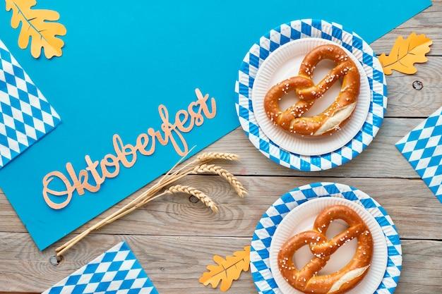 Oktoberfest rustique avec des prezels dans des assiettes en papier et des feuilles d'automne orange