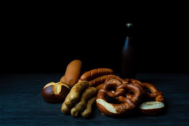 Oktoberfest saucisses bretzels de style nourriture sombre et bouteille de bière sur table en bois