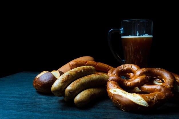 Oktoberfest saucisses bretzels de style nourriture sombre et pot de bière sur table en bois