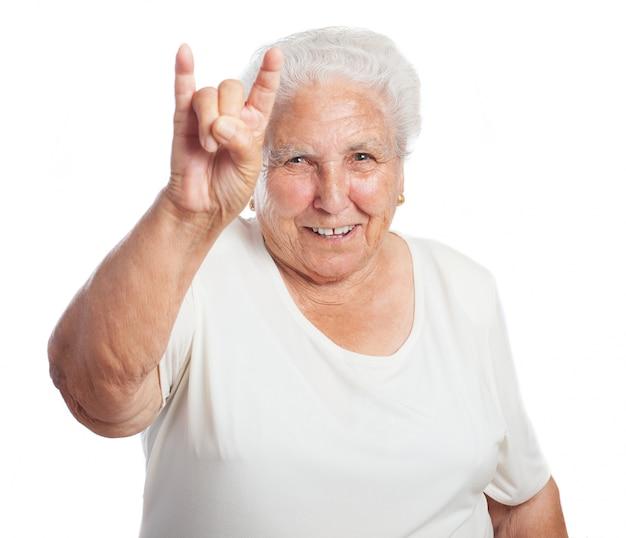 Old femme faisant des cornes à la main