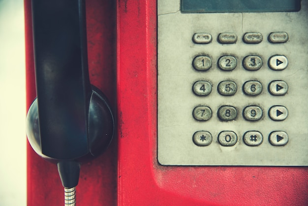 Old rundown red payphone