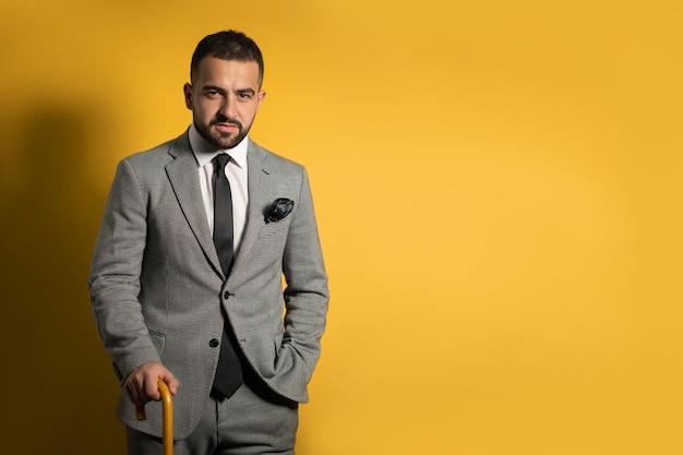 Old school trendy élégant beau jeune homme vêtu d'un costume gris avec une main levée debout avec canne ou parapluie à la main isolé sur mur jaune