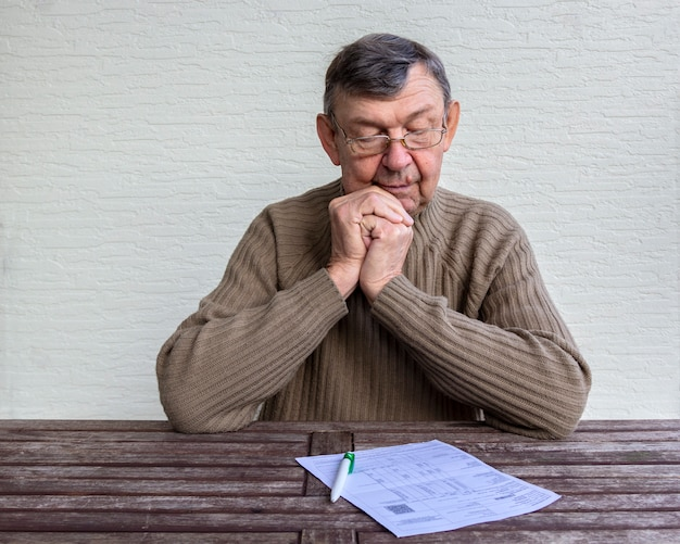 Old senior regarde avec surprise sur les factures de services publics