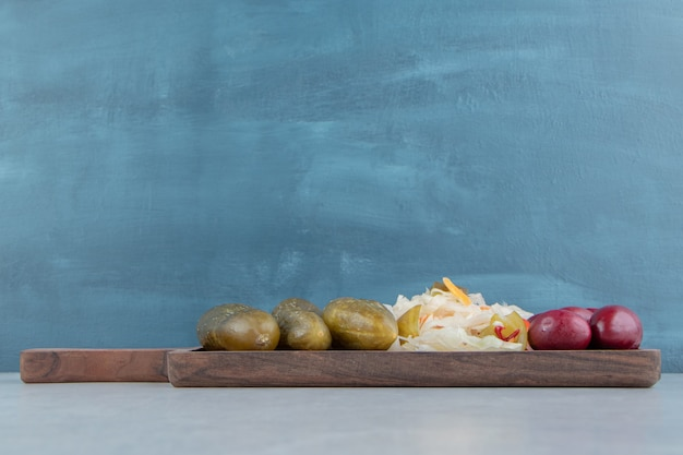 Olive, chou et concombre marinés sur une planche