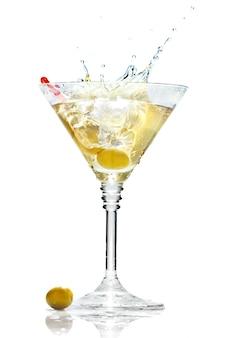 Olive éclaboussant sur un verre à martini isolé