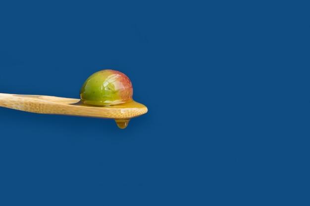 Olive mature sur une cuillère en bois sur fond bleu