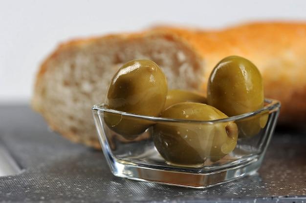 Olives, baguette et gros plan d'huile d'olive