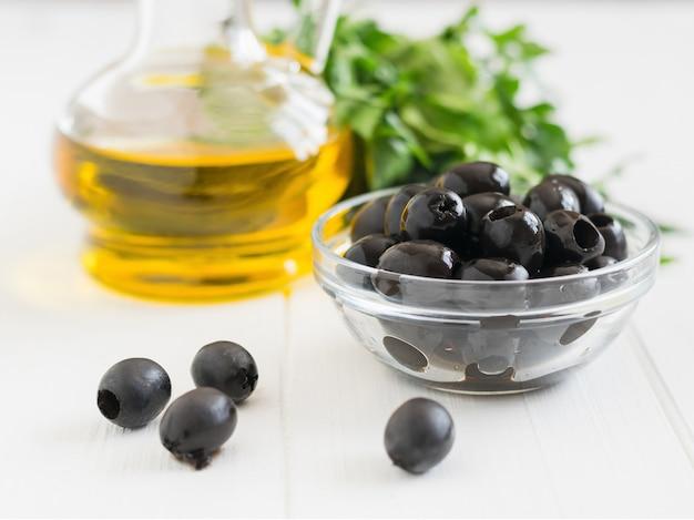Olives et une bouteille d'huile d'olive sur une table en bois blanc.