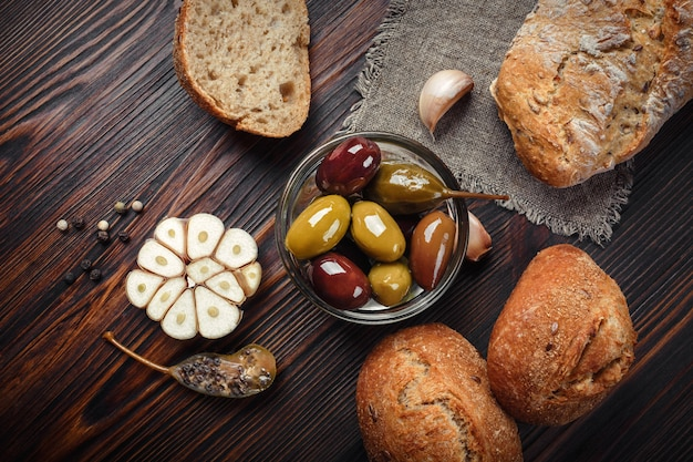 Olives et câpres ail poivre sur une table en bois