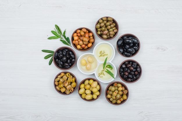 Olives colorées et huile d'olive avec des feuilles d'olivier dans une argile et des bols blancs sur planche de bois blanc, vue de dessus.
