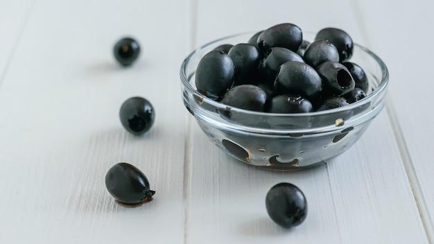 Olives en conserve dans un bol en verre sur une table en bois blanc.