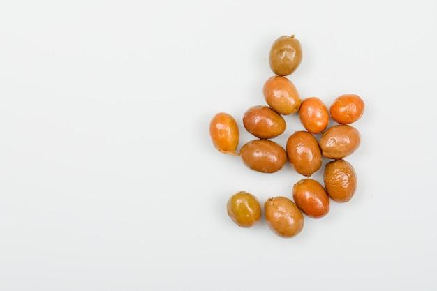 Olives de couleur claire sur blanc. vue de dessus.