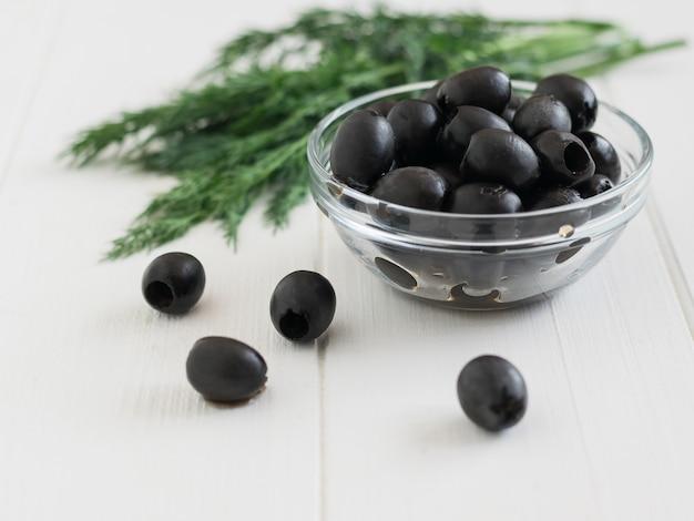 Olives dans un bol en verre et un gros bouquet de fenouil sur une table blanche.
