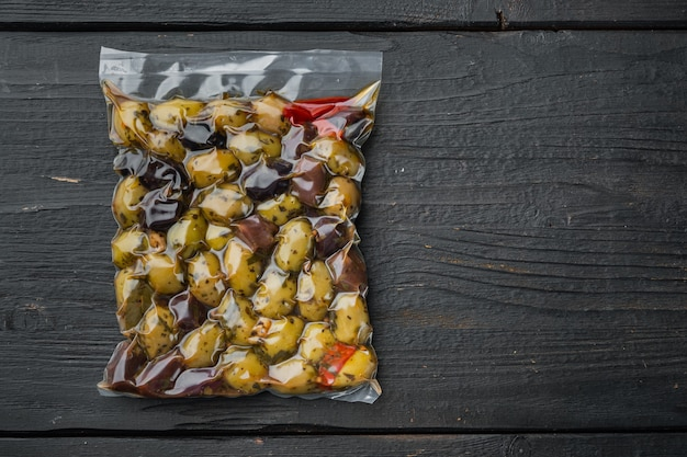 Olives d'espagne fraîches, sur fond de bois noir, mise à plat avec espace de copie pour le texte