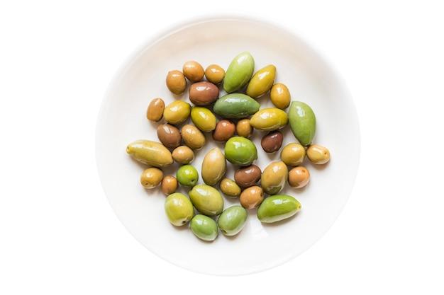 Olives fraîches aux fruits d'olive dénoyautées en assiette sur le veggie de table
