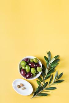 Olives fraîches et branche d'olivier sur une table