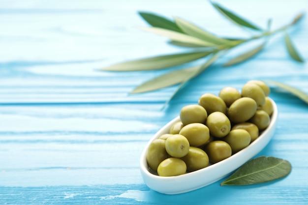 Olives fraîches dans un bol avec des feuilles sur fond bleu avec espace de copie.
