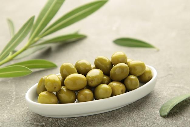 Olives fraîches dans un bol avec des feuilles sur fond gris avec espace de copie.