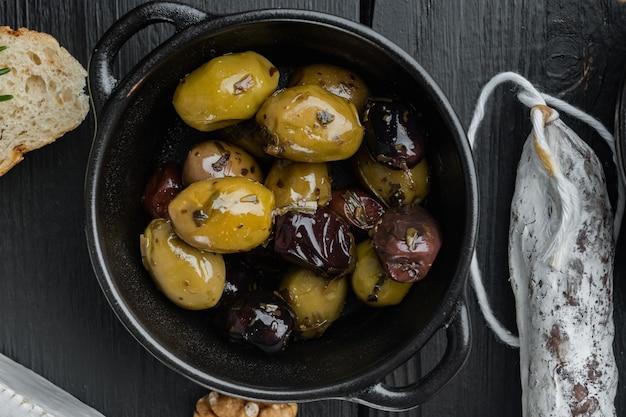 Olives fraîches méditerranéennes, sur table en bois noir, mise à plat
