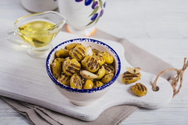 Olives grillées à l'ail, huile d'olive et épices sur fond de bois rustique blanc