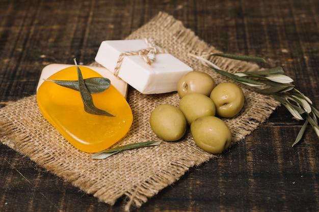 Olives de gros plan avec des barres de savon sur un sac