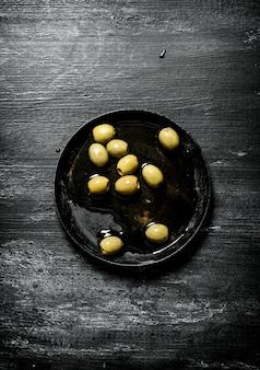 Olives à l'huile d'olive sur fond noir rustique