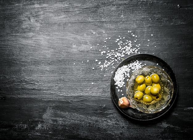 Olives à l'huile et sel sur fond noir rustique
