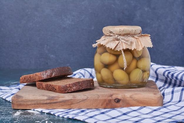 Olives marinées dans un bocal en verre avec des tranches de pain noir sur bleu.