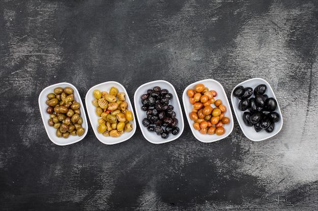 Olives marinées fraîches dans une vue de dessus des plaques blanches sur grunge gris foncé