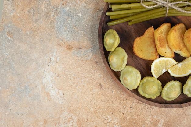 Olives marinées, haricots verts et pommes de terre frites sur plaque en bois