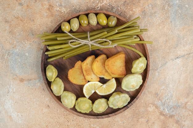 Olives marinées, haricots verts et pommes de terre frites sur plaque de bois