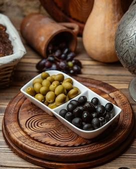 Olives marinées noires et vertes dans un bol blanc.