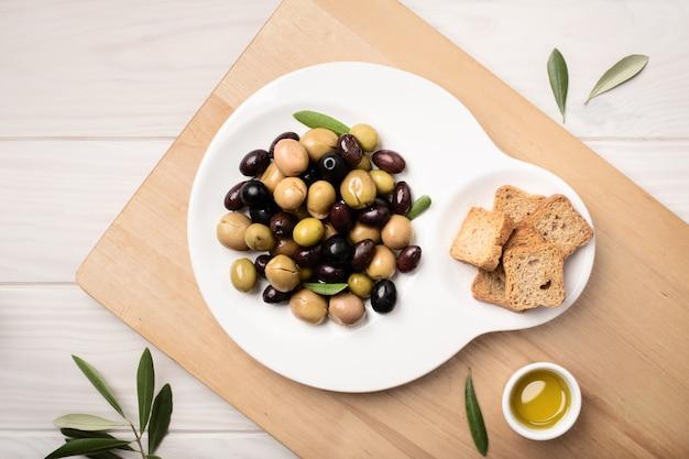 Olives marinées en plaque sur une table en bois.
