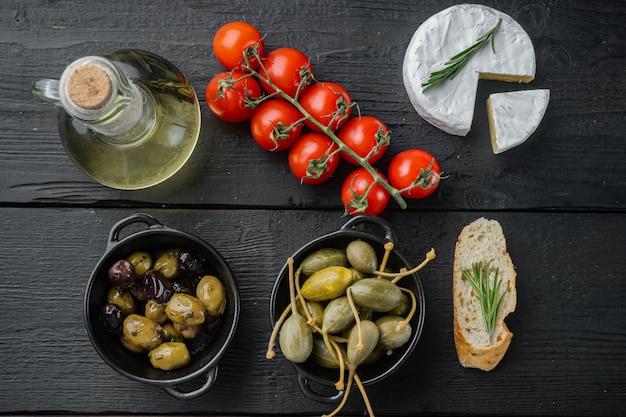 Olives méditerranéennes et câpres aux herbes, sur table en bois noir, vue du dessus