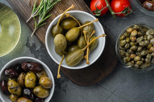Olives méditerranéennes et câpres aux herbes, sur table grise, vue du dessus