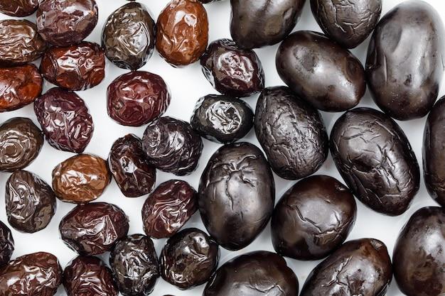Olives noires et brunes sur blanc. fermer.