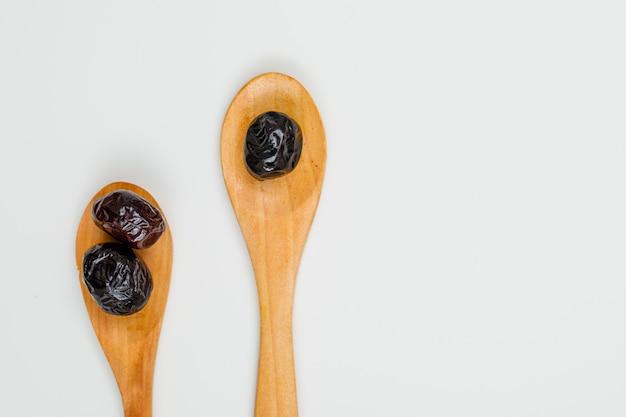 Olives noires et brunes dans une cuillère en bois blanc. fermer.
