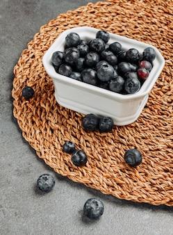 Olives noires dans un bol carré sur un dessous de plat en rotin et fond gris. vue grand angle.