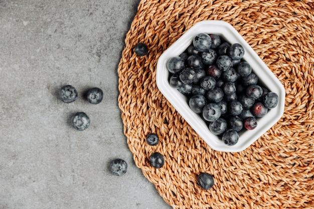Olives noires dans un bol carré vue de dessus sur un dessous de plat en rotin et fond gris