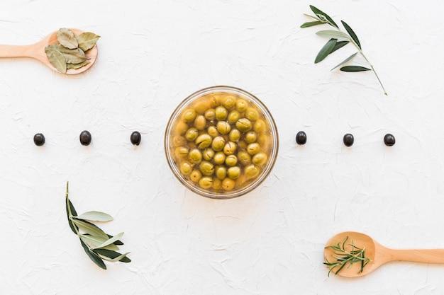 Olives noires et vertes aux herbes sur une cuillère en bois sur le fond blanc