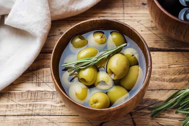 Olives noires et vertes dans des bols en bois sur une table en bois