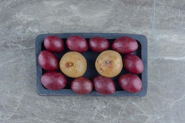 Olives et pommes marinées sur plaque de bois