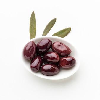 Olives pourpres sur plaque avec feuilles