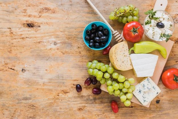 Olives, tomates, piment vert avec plateau de fromages sur table en bois