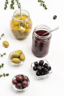 Olives vertes, brunes et noires en conserve sur table. brins de thym. vue de dessus