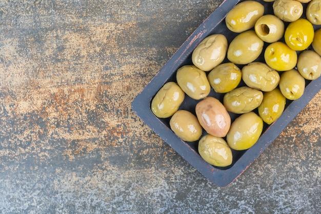 Olives vertes conservées sur une assiette en bois.