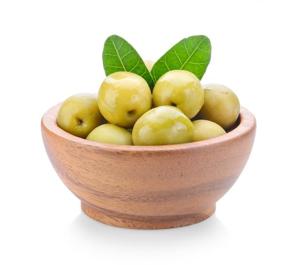 Olives vertes dans un bol en bois sur fond blanc