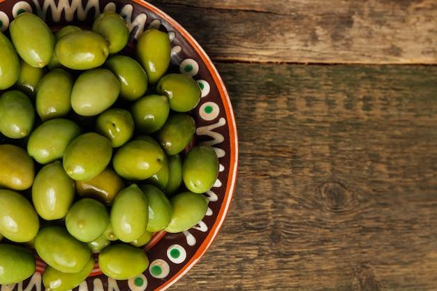 Olives vertes dans un bol brun sur une surface en bois