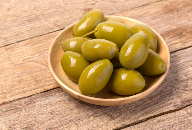 Les olives vertes dans un bol sur fond de bois.